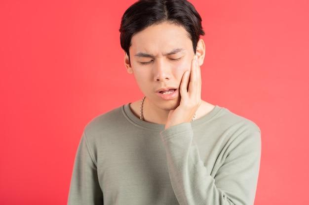 Zdjęcie przystojnego mężczyzny z azji cierpiącego na próchnicę