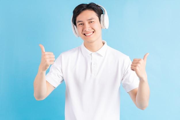 Zdjęcie przystojnego mężczyzny z azji, słuchając muzyki i używając kciuków do góry