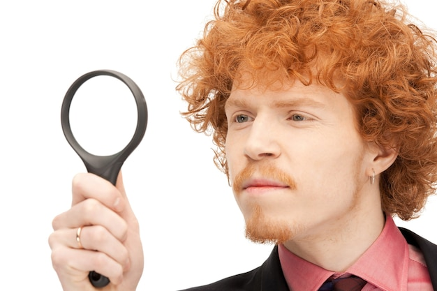 Zdjęcie przystojnego mężczyzny ze szkłem powiększającym