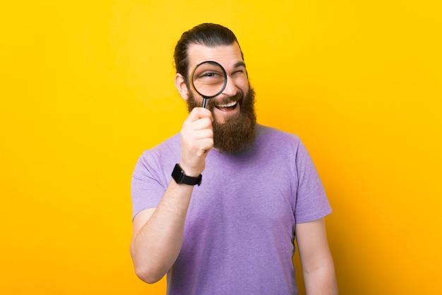 Zdjęcie przystojnego młodego brodatego mężczyzny patrzącego na ciebie przez szkło powiększające