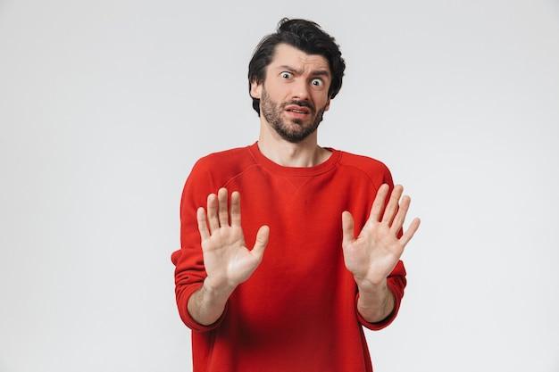 Zdjęcie przystojnego młodego przestraszonego mężczyzny pozującego na białej ścianie wykonać gest stopu.