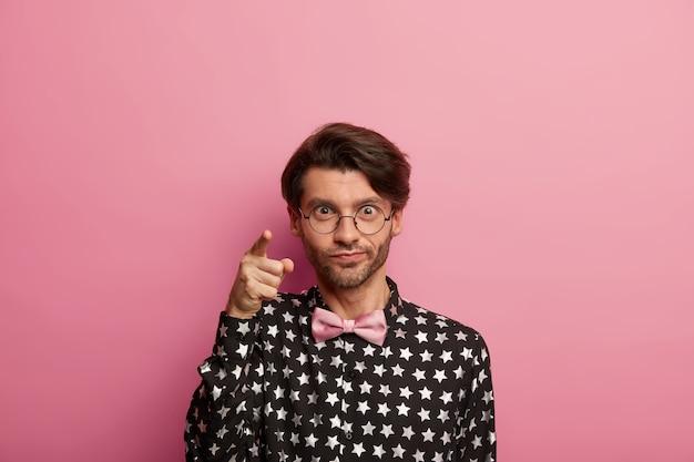 Zdjęcie przystojnego, nieogolonego mężczyzny wskazuje na aparat, patrzy bezpośrednio na ciebie, nosi okrągłe, duże okulary, koszulę i muszkę