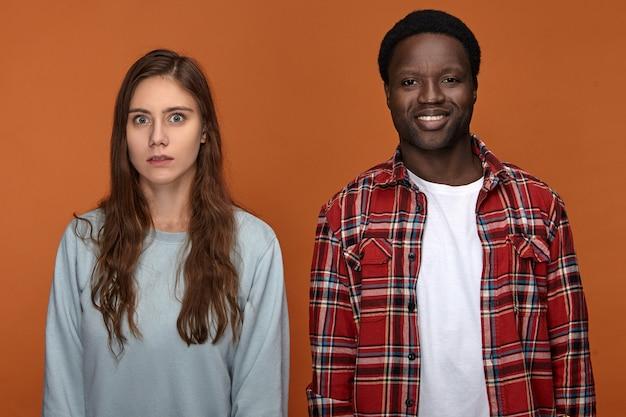 Zdjęcie przystojnego, pozytywnego, młodego, ciemnoskórego mężczyzny, uśmiechniętego, stojącego obok emocjonalnej białej dziewczyny z długimi luźnymi fryzurami, który patrzy z przerażonym wyrazem twarzy