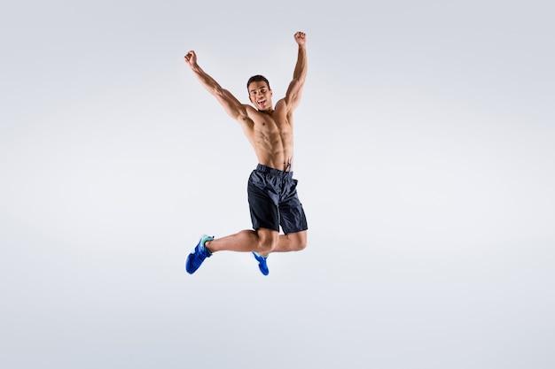 Zdjęcie przystojnego sportowca, ciemnoskórego faceta, nagiej klatki piersiowej, podskakującego wysoko, biegnącego szybkim sprintem