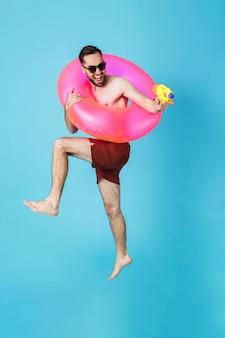 Zdjęcie przystojnego turysty bez koszuli noszącego gumowy pierścień uśmiechający się podczas zabawy z pistoletem na wodę na białym tle