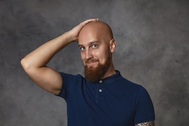 Zdjęcie przystojnego, uroczego faceta z krzaczastą brodą, uśmiechającego się nieśmiało i trzymającego rękę na ogolonej łysinie, proszącego śliczną kobietę o randkę. portret szczęśliwy atrakcyjny brodaty facet czuje się dumny z fryzury