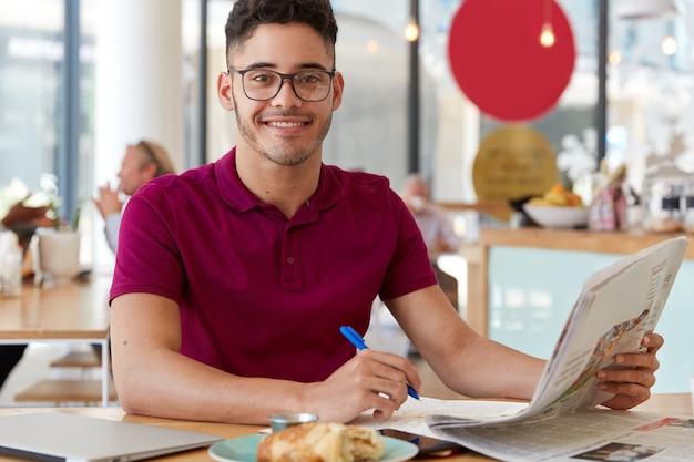 Zdjęcie przystojnego, zadowolonego faceta czyta najnowsze wiadomości w gazecie, zapisuje notatki w notatniku, nosi okulary i koszulkę, cieszy się pysznym rogalikiem. ludzie i koncepcja pracy
