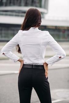 Zdjęcie przystojnej kobiety rasy kaukaskiej z długimi ciemnymi falującymi włosami w białej koszuli, czarnych spodniach i szpilkach patrzy na wysoki budynek