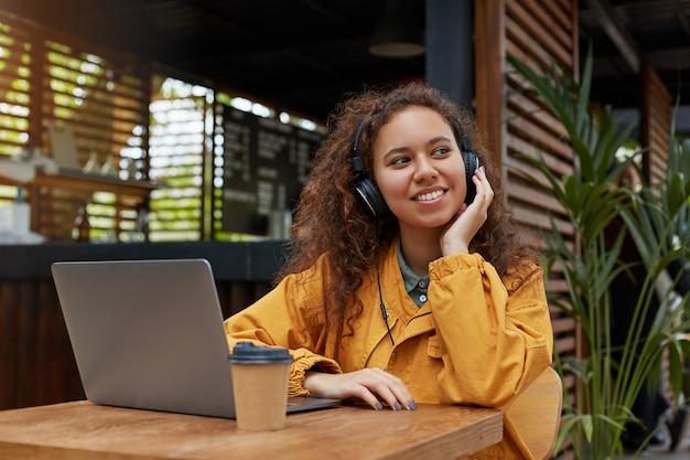 Zdjęcie przystojnej młodej ciemnoskórej kręconej kobiety siedzącej na tarasie kawiarni, słuchającej muzyki i śniącej, ubranej w żółty płaszcz, pijącej kawę, pracującej przy laptopie.