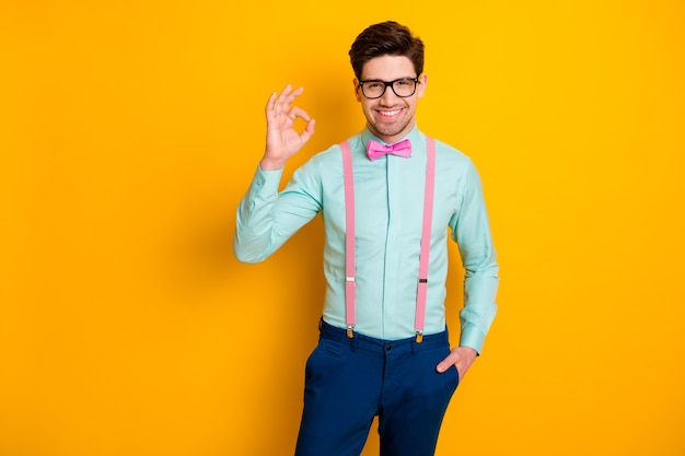 Zdjęcie przystojny fajne ubrania facet chłopak pewna siebie osoba pokazująca symbol okey wyrazić zgodę nosić specyfikacje koszula szelki muszka spodnie na białym tle żółty kolor tło