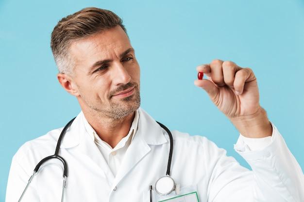 Zdjęcie przystojny lekarz ubrany w biały fartuch trzymając w ręku jedną pigułkę, stojący na białym tle nad niebieską ścianą