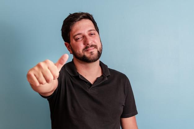 Zdjęcie przystojny mężczyzna uśmiecha się do kamery z kciukiem do góry