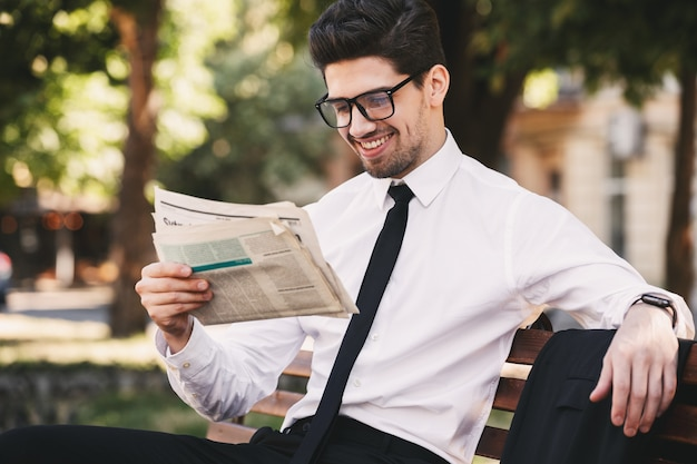 Zdjęcie przystojny mężczyzna w garniturze siedzi na ławce w zielonym parku i czyta gazetę w słoneczny dzień