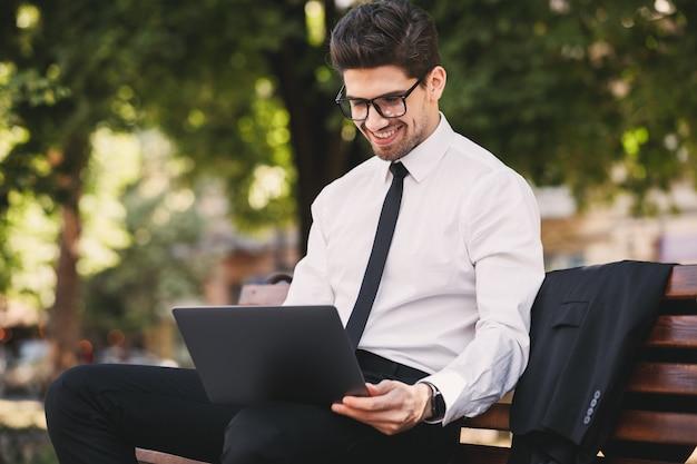Zdjęcie przystojny mężczyzna w garniturze siedzi na ławce w zielonym parku i pracuje na laptopie w słoneczny dzień