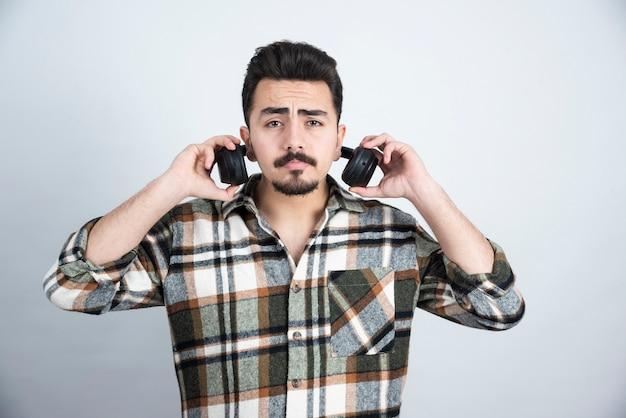 Zdjęcie przystojny mężczyzna ze słuchawkami stojąc i patrząc na białą ścianę.