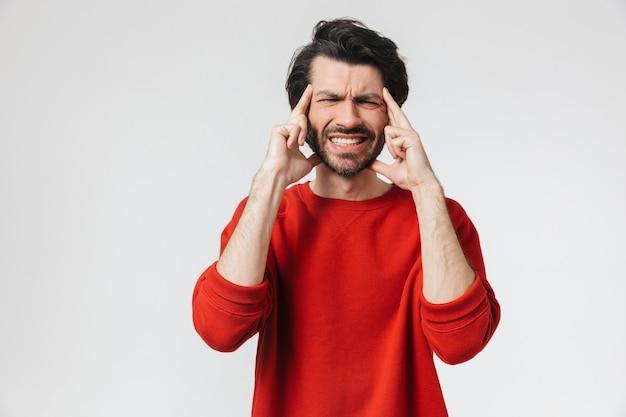 Zdjęcie przystojny młody niezadowolony mężczyzna z bólem głowy, pozowanie na białej ścianie.