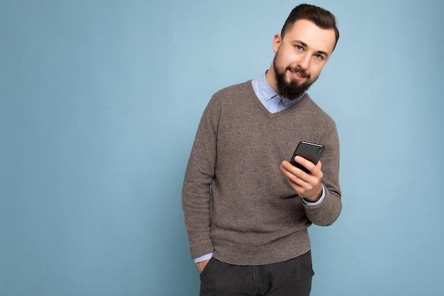 Zdjęcie przystojny, przystojny brunet brodaty młody człowiek ubrany w szary sweter i niebieską koszulę na białym tle