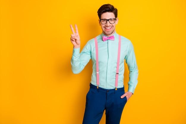 Zdjęcie przystojnych fajnych ubrań przyjazna dla faceta osoba pokaż symbol vsign witam wszystkich przyjaciół po kwarantannie nosić specyfikacje koszula szelki muszka spodnie na białym tle żółty kolor tło