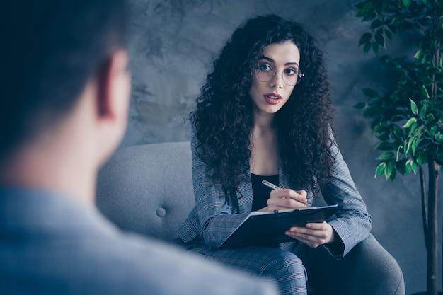 Zdjęcie psychologa dziewczyna siedzi na krześle konsultującym klienta na szarym tle