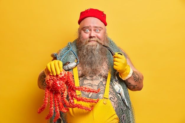 Zdjęcie pulchnego, brodatego marynarza złapanego na wielką czerwoną ośmiornicę nosi sieć rybacką ubraną w kombinezon i ma wytatuowane ciało