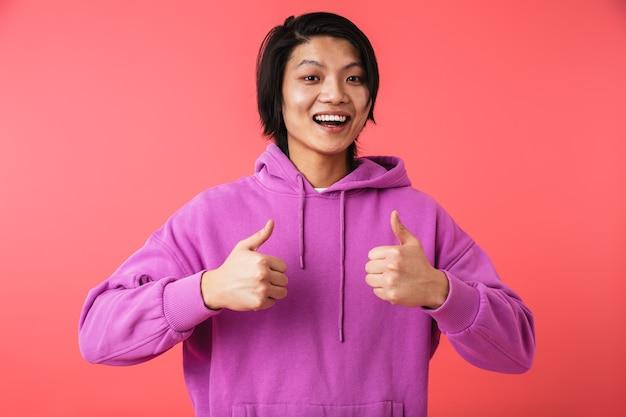Zdjęcie radosnego azjatyckiego faceta noszącego bluzę, radującego się i pokazującego kciuki w górze na białym tle nad czerwoną ścianą