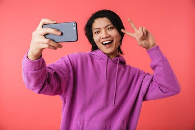 Zdjęcie radosnego azjatyckiego faceta w bluzie pokazującej znak pokoju i robiący selfie na smartfonie na białym tle nad czerwoną ścianą