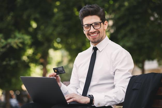 Zdjęcie radosnego biznesmena w garniturze siedzi na ławce w zielonym parku i pracuje na laptopie w słoneczny dzień