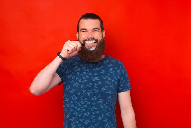 Zdjęcie radosnego brodatego mężczyzny pokazującego swój ząbkowany uśmiech przez szkło powiększające