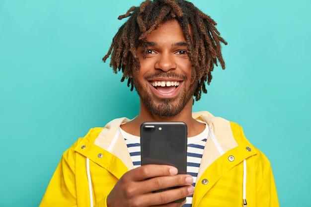 Zdjęcie radosnego etnicznego faceta z dredami wykorzystuje nowoczesny telefon komórkowy do przesyłania wiadomości online
