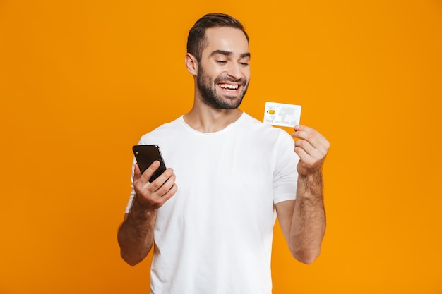 Zdjęcie radosnego mężczyzny lat 30. w casual, trzymając smartfon i kartę kredytową, na białym tle