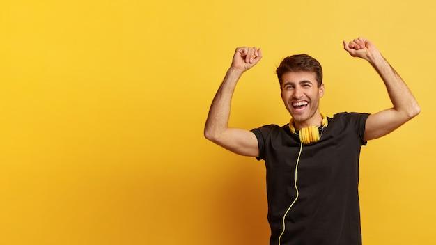 Zdjęcie radosnego mężczyzny rasy kaukaskiej podnosi ręce z triumfem