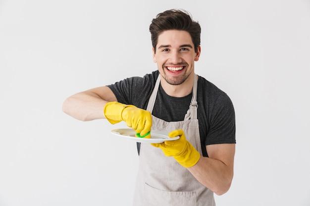 Zdjęcie radosnego młodego mężczyzny w żółtych gumowych rękawiczkach do ochrony rąk podczas mycia naczyń podczas sprzątania domu na białym tle nad białym