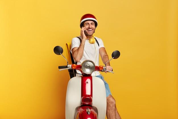 Zdjęcie radosnego przystojnego kierowcy płci męskiej na skuterze z czerwonym kaskiem