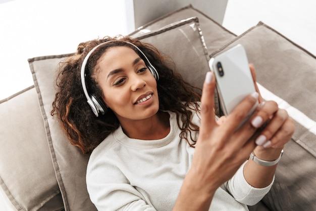 Zdjęcie radosnej afroamerykanki noszącej słuchawki, trzymając telefon komórkowy, leżąc na kanapie w jasnym mieszkaniu