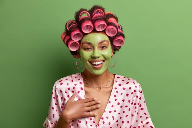 Zdjęcie radosnej, beztroskiej kobiety, która lubi zabiegi kosmetyczne w domu, nosi zieloną maseczkę na twarz dla zdrowej skóry, nosi lokówki, ubrana w jedwabną suknię, słyszy coś zabawnego, pozuje w domu