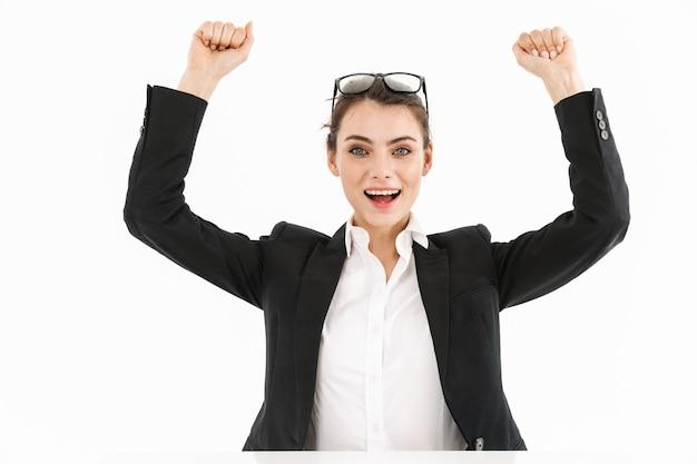 Zdjęcie radosnej bizneswoman pracownic ubranej w strój wizytowy podczas pracy i siedzącej przy biurku w biurze na białym tle nad białą ścianą