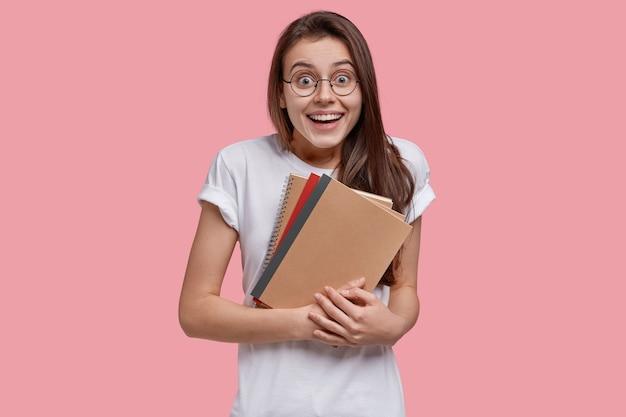 Zdjęcie radosnej ciemnowłosej kobiety trzymającej spiralny notatnik, szeroko się uśmiecha