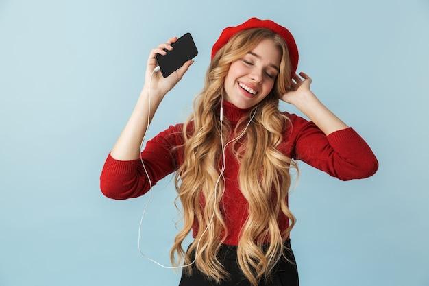 Zdjęcie radosnej dziewczyny 20s noszących słuchawki do słuchania muzyki na telefonie komórkowym na białym tle