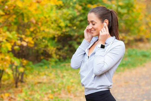Zdjęcie radosnej kobiety fitness z lat 30. w odzieży sportowej dotykający bluetooth earpod i trzymający telefon komórkowy podczas odpoczynku w zielonym parku