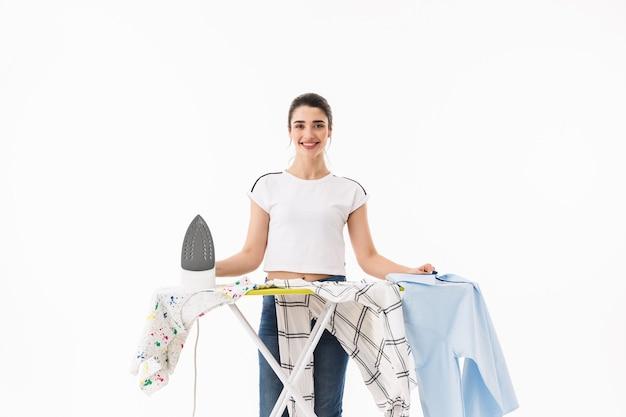 Zdjęcie radosnej kobiety gospodyni domowej w wieku 20 lat w swobodnych dżinsach prasujących czyste ubrania na desce odizolowanej nad białą ścianą