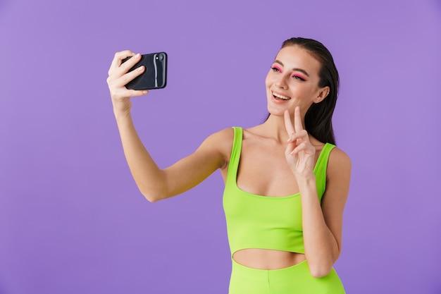 Zdjęcie radosnej młodej kobiety robiącej zdjęcie selfie na smartfonie i wskazującego znak pokoju