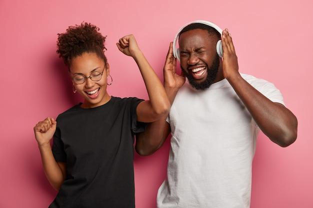 Zdjęcie radosnej pary afroamerykanów, baw się i tańcz do głośnej muzyki, świętuje pozytywnie zdany egzamin, korzysta ze słuchawek