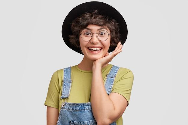 Zdjęcie radosnej, uroczej młodej projektantki, odnoszącej sukcesy, uśmiecha się radośnie i patrzy oczami pełnymi szczęścia