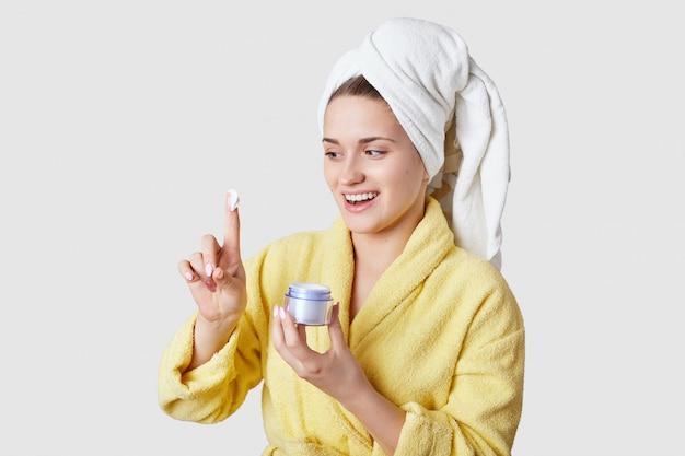 Zdjęcie radosnej zdrowej kobiety trzyma pojemnik z kremem, zadowolony z jego dobrego efektu, ubrany w codzienne ubrania, szlafrok i ręcznik, ma zabiegi kosmetyczne w domu, na białym tle nad białą ścianą