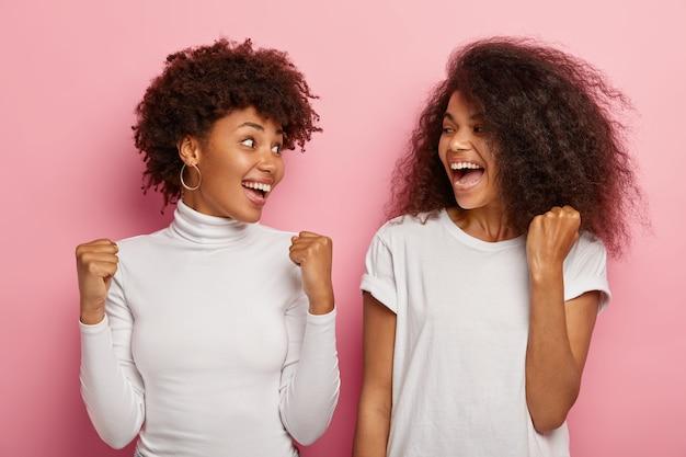 Zdjęcie radosnych kobiet patrzą na siebie, unoszą zaciśnięte pięści z triumfem, pokazują gest zwycięstwa