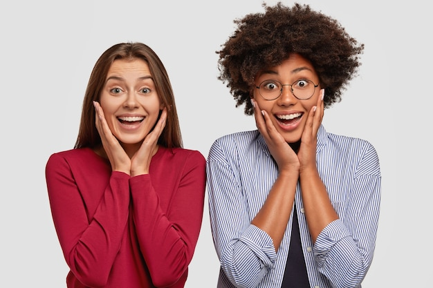 Zdjęcie radosnych zdumionych dwóch międzyrasowych kobiet trzymających obie dłonie na policzkach