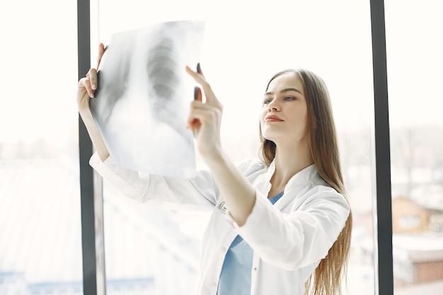 Zdjęcie rentgenowskie na oknie. kobieta z długimi włosami. lekarz w odzieży roboczej.
