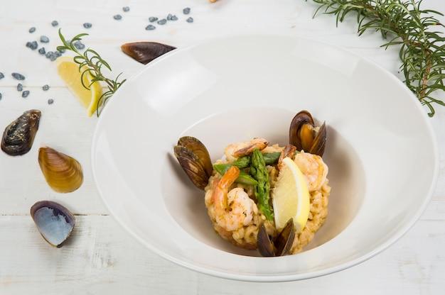 Zdjęcie risotto z owocami morza na turkusowej fakturze, z widelcem i łyżką, lampką białego wina i miejscem na tekst