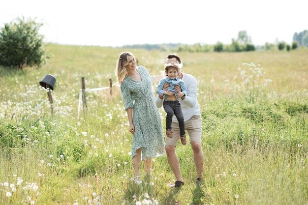 Zdjęcie rodziny cieszącej się letnim dniem na łące kwiatowej, rodzice kochają swojego małego synka 3 lata