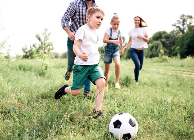 Zdjęcie rodziny grającej razem w piłkę nożną. chłopiec biegnie przed wszystkimi. za nim biegnie mężczyzna i dziewczyny. bawią się na łące.